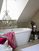 A chandelier above a bathtub in a bathroom with a skylight