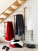 Hanging towels, a swim bag and a pair of scales in a tiled bathroom