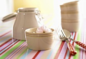 Cream coloured bowls and cutlery on a striped surface