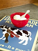 Schale mit Vanilleeis auf einem Werbeschild für Eiscreme