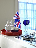 Bowls, a glass jug and a Union flag on a red tray next to a gas cooker