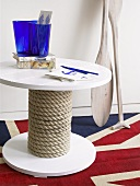 A round, maritime themed table and paddles on a Union Jack rug