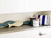 Decorative fish on a shelf with tooth mugs and a cosmetics bag