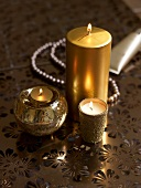 Decorative gold candles and a pearl necklace