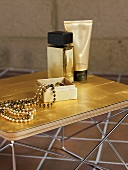 A jewellery box and a pearl necklace with a golden perfume bottle and a tube of cream