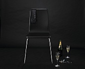 A glove over the back of a black chair with champagne and precious stone next to it