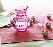 A pink carafe, a glass and small candles in bowls as table decoration
