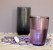Two glasses and a a purple beaded necklace