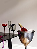A bottle of rose champagne in a champagne chiller with glasses on a black table