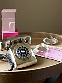A silver telephone and a paper weight on a leather covered tray