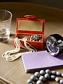 A necklace in a jewellery box, an alarm clock, a diary and a glass on a leather-covered tray