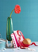 A gerbera in a green vase, paper decoration and a brioche