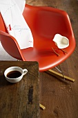 A red rocking chair with a miniature replica version in white and a cup of coffee on a wooden table
