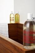 Three bottles of liquid soap on the edge of a wash basin