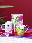 Two tea cups and a tea tin