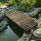 Eine kleine Brücke über einem schmalen Teich