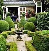 Kleiner mit niedrigen Buchsbaumhecken in Formschnitt und mit Fuchsia in einer Pflanzenschale aus Stein