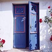 Weisses Landhäuschen mit blauer Doppeltür und Kletterrosen