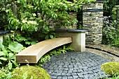 Geschwungene Holzbank auf einer kleinen gepflasterten Terrasse in einem ummauerten Garten