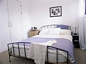 A double bed with a metal bedstead in a white bedroom