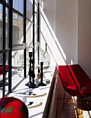 A set of black candle sticks on a window sill and a red Bauhaus-style armchair
