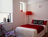 A floor lamp with a red shade next to a double bed with black and white cushions and a red quilt