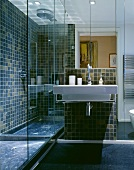 A modern bathroom with a designer wash basin and a mirrored cabinet next to a glazed shower area