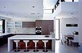 Open-plan living with a white counter and bar stools in a kitchen with a designer dining area
