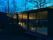 A newly built house with a floor-to-ceiling glass facade in the evening