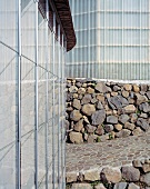 A corner of a newly built house with a natural stone wall