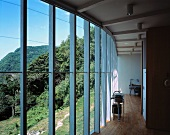 An open living room in a newly built house with a glass facade and a panoramic view