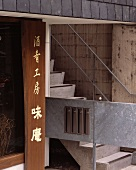 Outdoor concrete steps and a bridge with metal banisters next to a wooden sign with Japanese characters