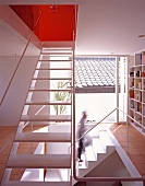 An open stairway with built in bookshelves and floor-to-ceiling windows