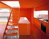A stairway dividing an open-plan, red-painted kitchen from a living room