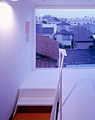 A stairwell and landing with a window and a view over the town