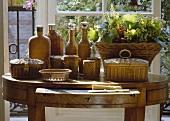 Verschiedene Körbe und Korbflaschen auf antikem Tisch