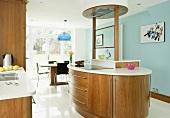 Freistehende Kochinsel in moderner Küche mit hellblauer Wand und Essplatz
