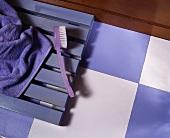 Violette Zahnbürste auf violettem Holzrost und auf Boden mit Schachbrettmuster