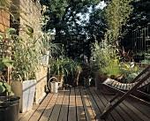 Liegestuhl und Pflanzentöpfe auf Holzterrasse
