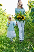 A tall girl and her little sister in a sunflower field