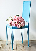 A bunch of pink roses on a blue chair