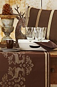 A Christmas table laid with a brown cloth, wine glasses and cups