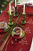 A Christmas table laid with a red cloth and candles