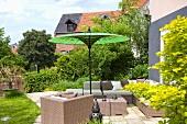 Korbmöbel auf Terrasse am Haus mit grünem Sonnenschirm