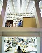 Blick durch Fenster auf arbeitende Menschen im Büro