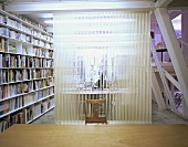An office with a transparent room divider and a built-in bookshelf