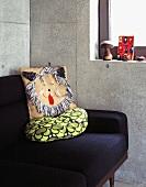 Detail of a sofa with a cushion against a concrete wall
