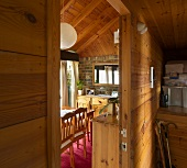 An anteroom in a wooden house with a view through an open door into a dining room