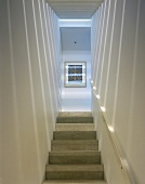 A narrow modern stairway with a play of light and shade on the wall