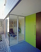 A green front door next to a glass facade of a newly built house